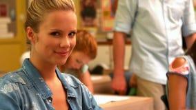 Blonder Student, der sich dreht, um an der Kamera zu lächeln stock video footage