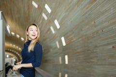 Blonder Student, der Smartphone im monophonischen Hintergrund hält Lizenzfreie Stockbilder
