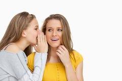 Blonder Student, der zu ihrem schönen Freund flüstert Stockbild