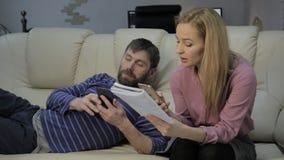 Blonder Student liest ihre Anmerkungen und ihren Freund, der auf Sofa und Gebrauch Smartphones sitzt stock video