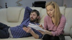 Blonder Student liest ihre Anmerkungen und ihren Freund, der auf Sofa und Gebrauch Smartphones sitzt stock footage