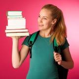 Blonder Student mit dem Stapel von Büchern und von Rucksack, glücklich, kn zu erhalten Lizenzfreies Stockbild