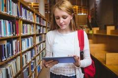 Blonder Student mit Rucksack unter Verwendung der Tablette in der Bibliothek Stockfotos