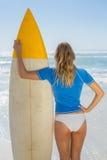 Blonder Surfer, der ihr Brett auf dem Strand hält Stockfotografie