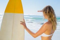 Blonder Surfer im weißen Bikini, der ihr Brett auf dem Strand hält Lizenzfreie Stockfotografie