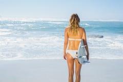 Blonder Surfer im weißen Bikini, der ihr Brett auf dem Strand hält Lizenzfreies Stockfoto