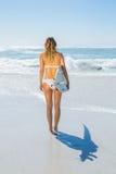 Blonder Surfer im weißen Bikini, der ihr Brett auf dem Strand hält Stockfotografie
