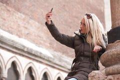 Blonder Tourist, der draußen ein selfie macht Lizenzfreie Stockfotos