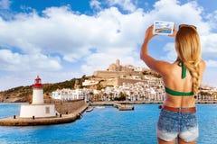 Blonder touristischer Fototabletten-PC in Ibiza-Skylinen Stockfotos