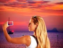 Blonder touristischer nehmender Smartphonephotographiesonnenuntergang Lizenzfreie Stockfotografie