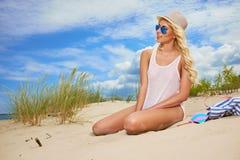 Blonder tragender Sonnenhut am Strand Stockfotografie