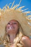 Blonder tragender Strohhut auf sonnigem Strand Lizenzfreie Stockfotos