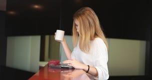 Blonder trinkender Kaffee, der entspannenden Lebensstil genießt Lizenzfreie Stockfotos