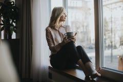 Blonder trinkender Kaffee der jungen Frau durch Fenster Lizenzfreies Stockfoto