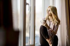 Blonder trinkender Kaffee der jungen Frau durch Fenster Lizenzfreie Stockfotografie