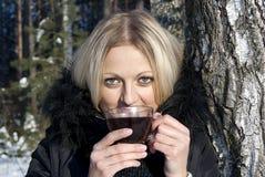 Blonder trinkender Tee des schönen Mädchens im Winter Stockfotografie