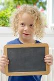 Blonder und gelockter Junge, der eine Tafel hält Lizenzfreies Stockfoto