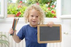 Blonder und gelockter Junge, der eine Tafel hält Stockbild
