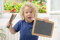 Blonder und gelockter Junge, der eine Tafel hält Stockfotografie