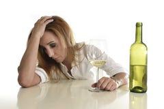Blonder vergeudeter und deprimierter Alkoholiker getrunkene Frau, die hoffnungsloses trauriges des Weißweinglases trinkt Stockbild