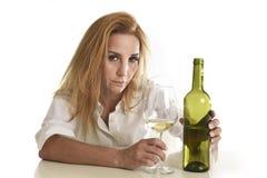 Blonder vergeudeter und deprimierter Alkoholiker getrunkene Frau, die hoffnungsloses trauriges des Weißweinglases trinkt Lizenzfreie Stockfotos
