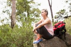 Blonder Wanderer, der auf Felsen sitzt und die Landschaft ansieht Stockfoto