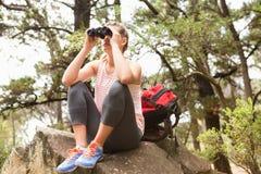 Blonder Wanderer, der auf Felsen sitzt und durch Ferngläser schaut Stockbild