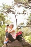 Blonder Wanderer, der auf Felsen sitzt und durch Ferngläser schaut Stockfotografie