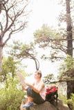 Blonder Wanderer, der auf Felsen sitzt und Karte liest Lizenzfreie Stockfotos