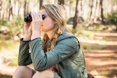 Blonder Wanderer, der durch Ferngläser sitzt und schaut Lizenzfreie Stockfotografie