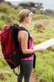 Blonder Wanderer mit der Karte, die nach Weg sucht Stockfotos