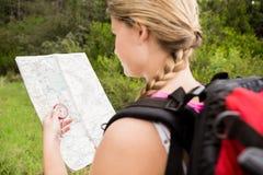 Blonder Wanderer mit Kompass- und Lesekarte Lizenzfreies Stockfoto