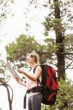 Blonder Wanderer mit Rucksacklesekarte Lizenzfreies Stockbild