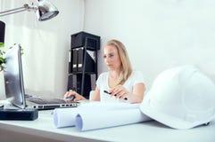 Blonder weiblicher Architekt arbeitet an ihren neuen Plänen Stockbild