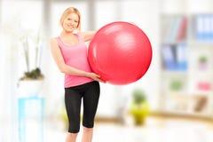 Blonder weiblicher Athlet, der einen pilates Ball und eine Aufstellung Innen hält Lizenzfreies Stockfoto