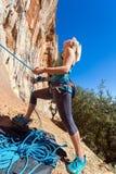 Blonder weiblicher Athlet, der ihren kletternden Partner mit Seil sichert Lizenzfreies Stockfoto