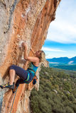 Blonder weiblicher Bergsteiger-steigender vertikaler orange Felsen Stockfoto