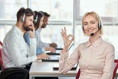 Blonder weiblicher Betreiber mit Kopfhörer zeigt okaygeste Stockfotografie