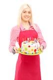 Blonder weiblicher Chef im Schutzblech, das einen köstlichen Kuchen hält Stockfotografie