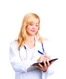 Blonder weiblicher Doktor, der Anmerkungen in den Papieren bildet Lizenzfreies Stockbild