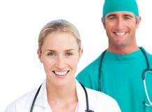 Blonder weiblicher Doktor und lächelnder Chirurg Stockfotos