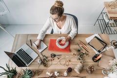 Blonder weiblicher Florist, der mit Laptop und trockenen Blumen am Arbeitsplatz arbeitet Lizenzfreies Stockfoto