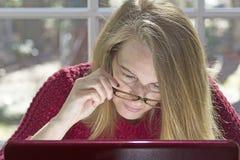 Blonder weiblicher Fokus auf Computer Stockfotos