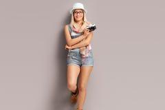 Blonder weiblicher Fotograf, der eine Kamera hält Stockbild