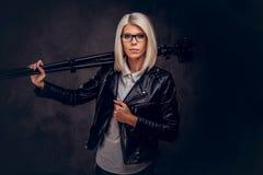 Blonder weiblicher Fotograf der Schönheit in den Gläsern, die eine weiße Bluse und eine schwarze Lederjacke tragen, hält eine Ber Lizenzfreie Stockfotos