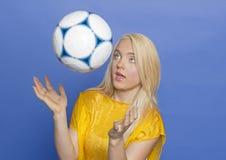 Blonder weiblicher Fußballspieler mit Kugel Lizenzfreie Stockfotos