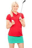 Blonder weiblicher Golfspieler, der einen Golfclub hält Lizenzfreies Stockfoto