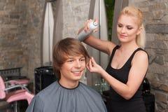 Blonder weiblicher Herrenfriseur, der Haarspray verwendet Stockbilder