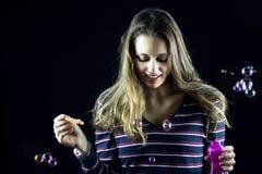 Blonder weiblicher Jugendlicher, der hinunter das Spielen mit Seifenblasen schaut Lizenzfreie Stockfotografie