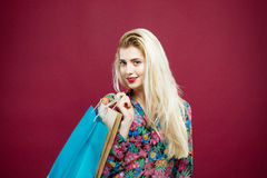 Blonder weiblicher Käufer im bunten Hemd hält Einkaufstaschen im Studio Glückliches Mädchen mit Lond-Haar und reizend Lächeln Lizenzfreies Stockfoto